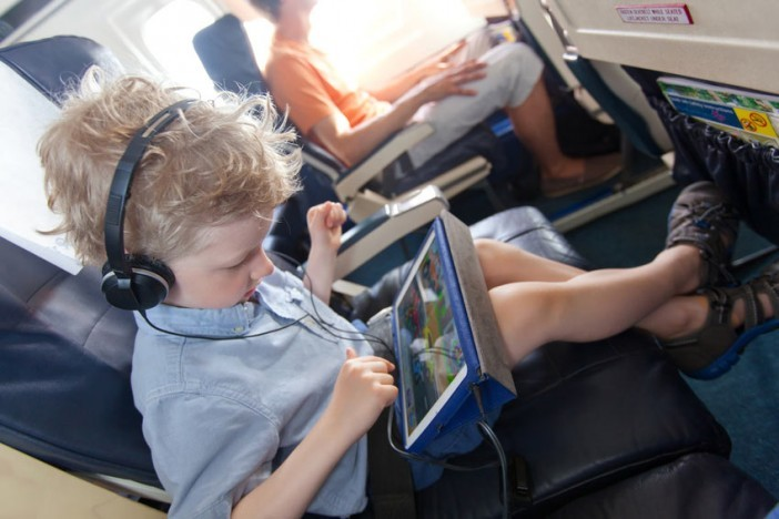 boy in plane with tablet