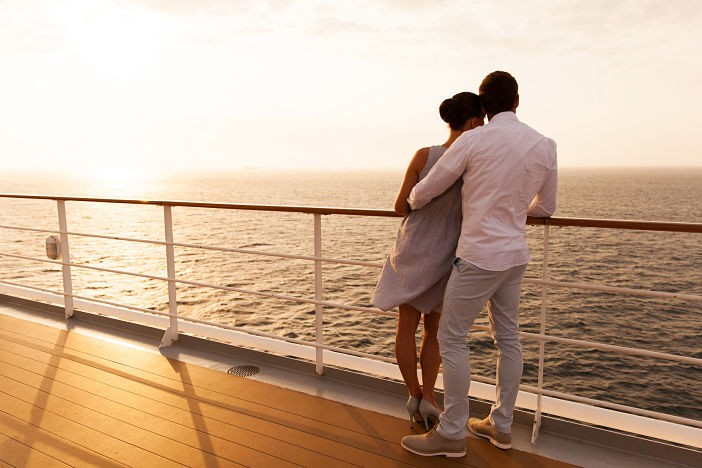 back view of young couple hugging at sunset on cruise ship
