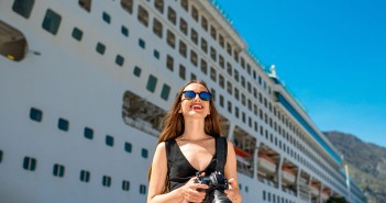 Young woman tourist photographing near the big cruise liner