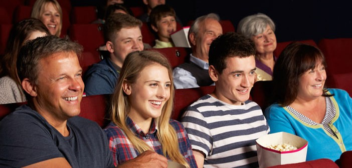 Teenage Family Watching Film In Cinema