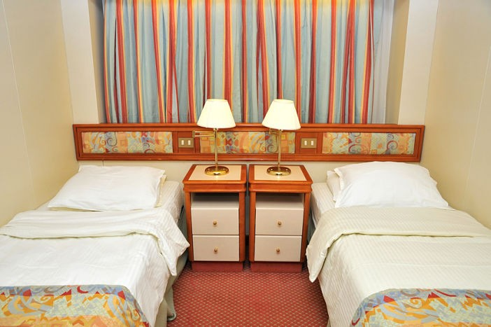 Front view of luxurious resort room with twin beds, in a cruise ship cabin.