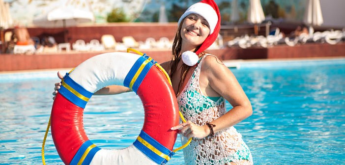 Beautiful girl in a swimming pool at a resort with a lifeline in Santa hats