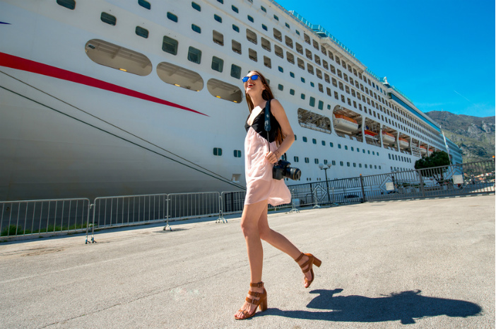 woman walking the decks with a cruise behind