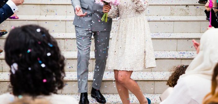 Married couple and wedding guests throwing confetti