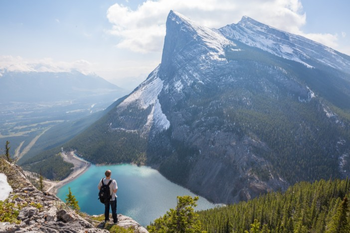 Man gazing at the Canadian Rocky Mountains in the distance