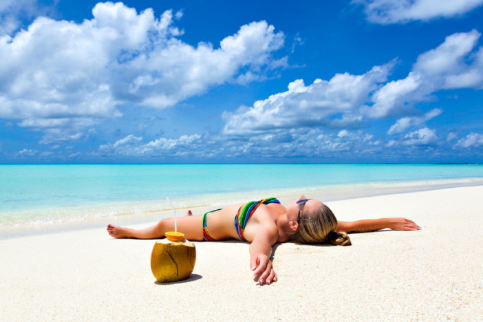 Young tanned woman girl lies on the beach with coconut on white sand by the tropical turquoise waters