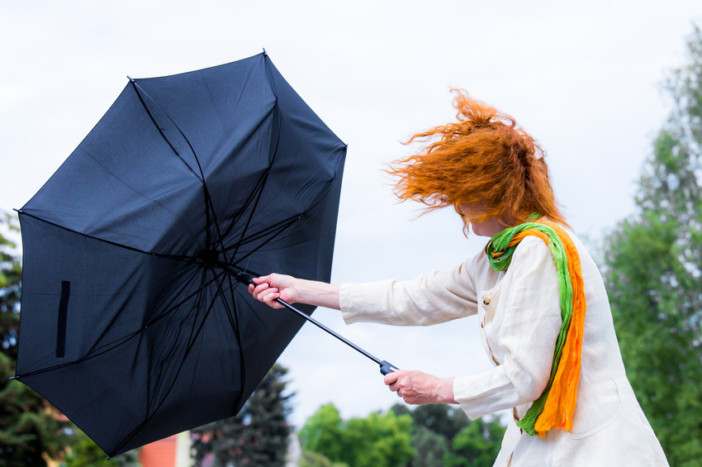 lady struggling with overturn umbrella during hurricane season