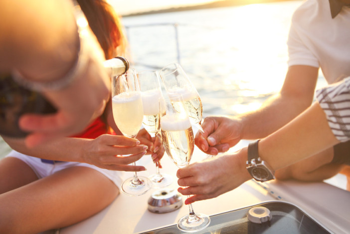 Happy friends with glasses of champagne on cruise. Vacation, travel, sea and friendship concept. Closeup.