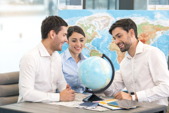 Young man tour agent with clients sitting in office travel agency choosing destination