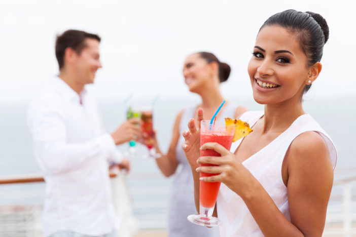 attractive girl holding a tropical cocktail on cruise