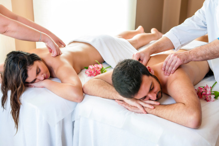 Close up of young couple enjoying simultaneous body massage in spa. Two therapists doing back massage on couple at the same time.