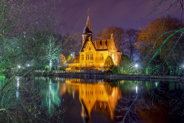 Old park Minnewater and lake in Bruges at night. One of the favorite tourist attractions.