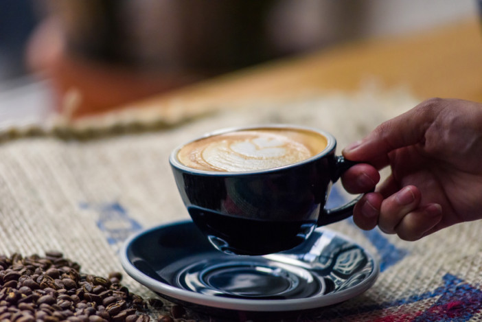 Perfectly brewed cappuccino and fresh roasted Arabica beans in the cozy atmosphere of a coffee shop. Professional barista or a client is going to taste a cup of coffee