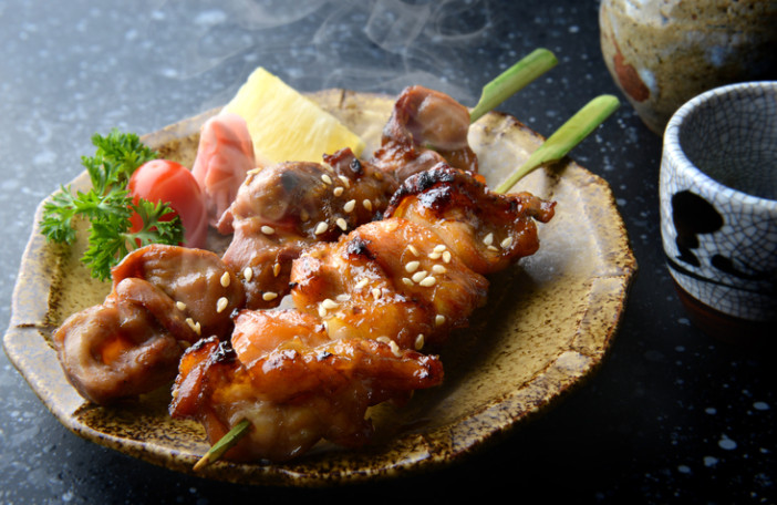 Japanese chicken grill or yakitori serve in izakaya style restourant set on Japanese style dish with flash lighting.