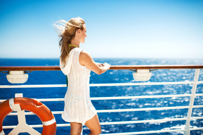 Smiling young woman enjoying her day on a ship and looking at view.