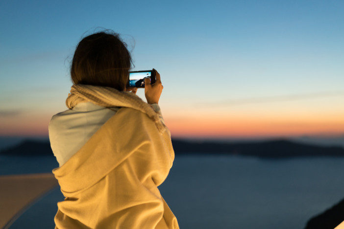 woman wearing a blanket because it is cold after sunset taking an image with her smartphone on a greek island