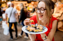 Young woman in red dress having lunch with mussels and rose wine sitting at the food market
