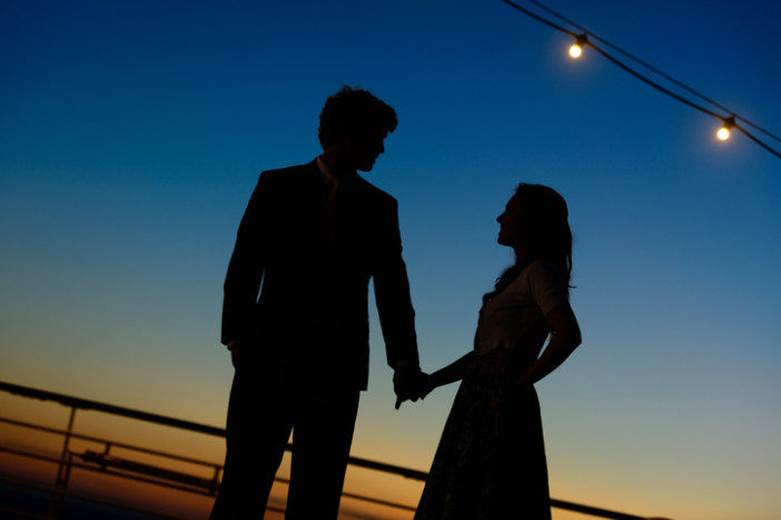 """Silhouette of man and woman holding hands on cruise ship, romantic moment."""
