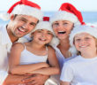 A family wearing white and red Christmas hats